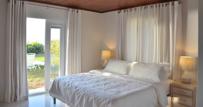 bedroom with bed and opened doors showing beach
