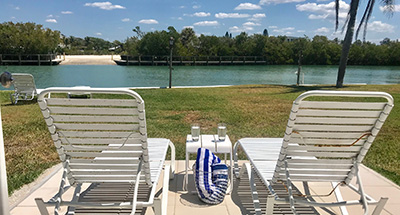 two white lounge chairs on the patio facing the Inlet